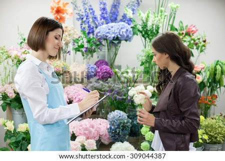 Attractive young florist is receiving an order from her female customer. She is writing the preferences and smiling. The girl is holding rose and looking at the selection of flowers with concentration - stock photo