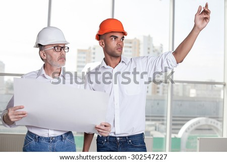 Attractive young foreman is explaining to senior architect his ideas about building. He is pointing his arm sideways with seriousness. Old man is holding blueprint and looking there with concentration - stock photo
