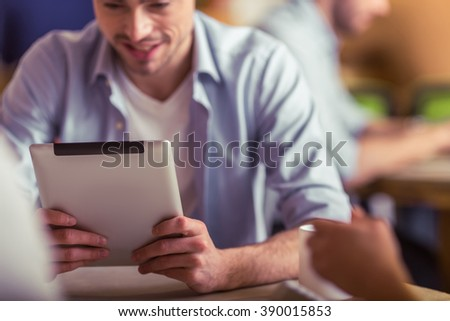 Attractive young freelancer is using a tablet and smiling while working with other people in cafe, close-up - stock photo