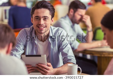 Attractive young freelancer is using a tablet, looking at camera and smiling while working with other people in cafe - stock photo