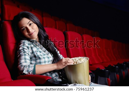 Attractive young girl at the cinema - stock photo