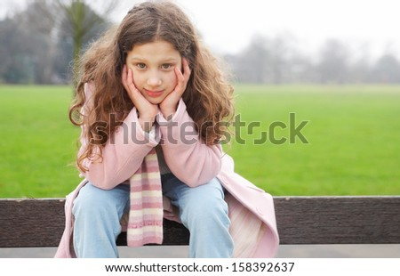 Attractive young girl being thoughtful while sitting on a wooden bench in a park and leaning on her hands during a cold winter day, outdoors. - stock photo