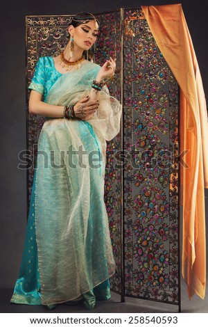 Attractive young girl dressed in sari standing near oriental screen with crystals - stock photo