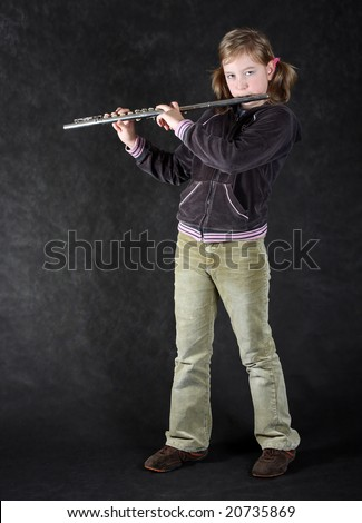 Attractive young girl flautist, flutist holding flute. Studio shot, black background. - stock photo