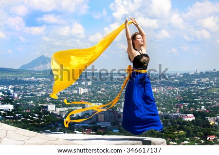 Attractive young Girl in a Blue skirt mysteriously flying over the city in the mountains and keeps fluttering yellow cloth. Not a collage - stock photo