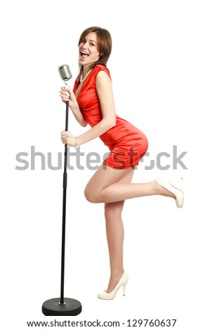 Attractive young girl in a red dress singing into a microphone, studio, isolated on white - stock photo