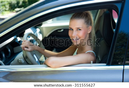 Attractive young girl in car at drivers position - stock photo