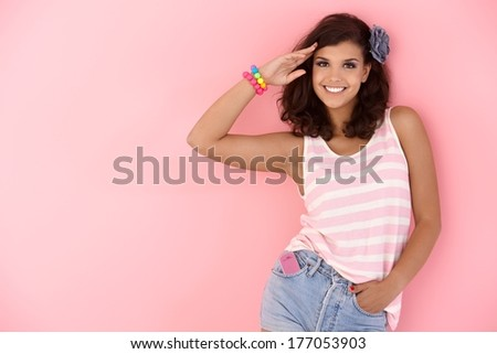 Attractive young girl posing over pink wall, smiling. - stock photo