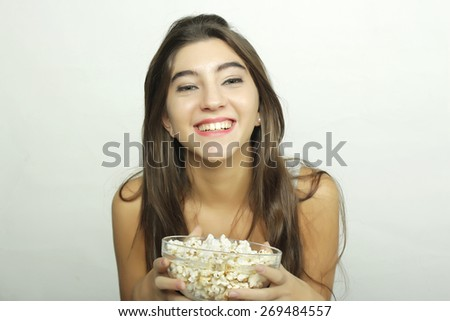Attractive young girl watching a movie with popcorn. Cinema concept - stock photo