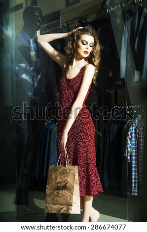 Attractive young girl with bright make up curly hair and red dress standing near shopping window indoor, vertical picture - stock photo