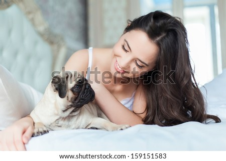 Attractive young girl with dog while laying on a bed - stock photo
