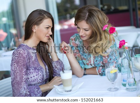 Attractive young gossip women drinking coffee - stock photo