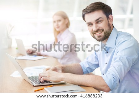 Attractive young guy is using a laptop - stock photo