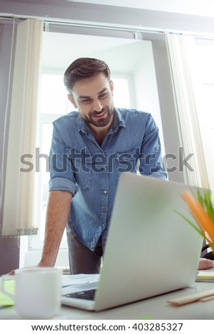 Attractive young guy is working on computer - stock photo