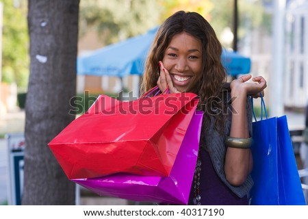 Attractive young happy African American woman walking in an urban city environment and carrying shopping bags. - stock photo
