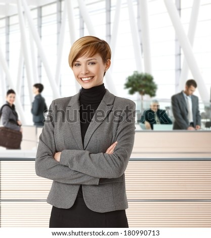 Attractive young happy businesswoman in office hallway. - stock photo