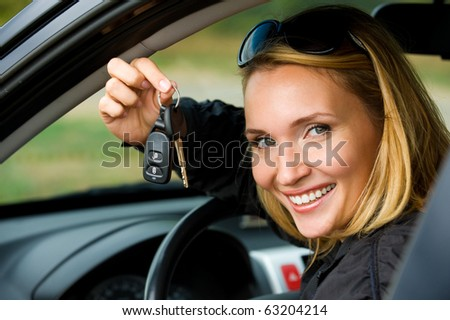 Attractive young happy woman shows keys from the new car - outdoors - stock photo