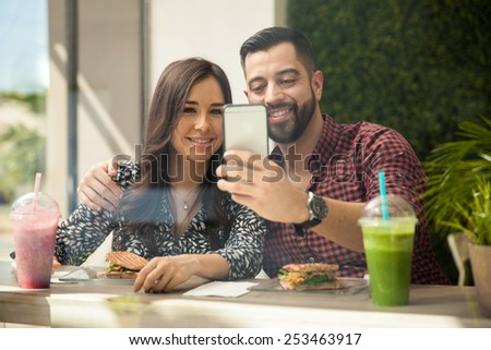 Attractive young Hispanic couple taking a selfie with a smartphone while eating lunch - stock photo