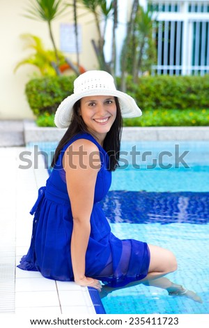 Attractive young hispanic woman in blue dress relaxing by the swimming pool - stock photo