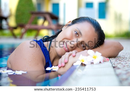 Attractive young hispanic woman in blue dress relaxing by the swimming pool surrounded by flowers - stock photo