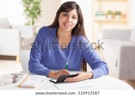 Attractive young Hispanic woman sitting at table paying bills and doing banking wearing blue sweater. - stock photo