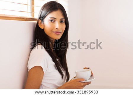 attractive young indian woman drinking tea at home - stock photo