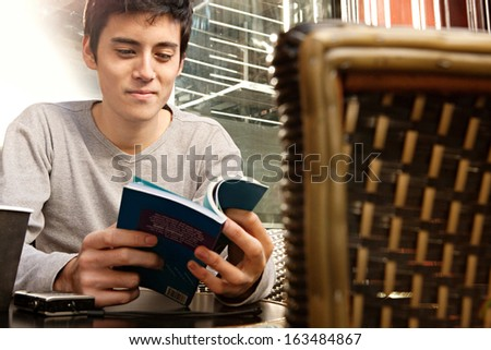 Attractive young Japanese tourist man sitting at a coffee shop in the city of London, having a coffee and reading a travel guide book, smiling outdoors during a sunny day. - stock photo
