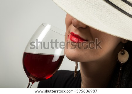 Attractive young lady model tasting red wine with elegance, - stock photo