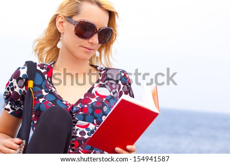 Attractive young lady reading a book by the sea. - stock photo