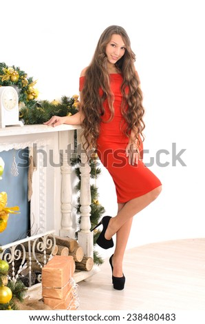 attractive young lady with long curly hair in red gown in christmas interior - stock photo