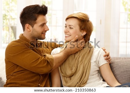 Attractive young loving couple embracing at home, smiling. - stock photo