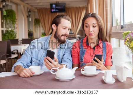 Attractive young loving couple is drinking tea in cafe. They are holding their mobile phones and messaging to someone. The guy is looking at female phone and smiling. His girlfriend is disappointed - stock photo