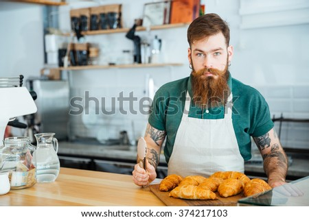 Attractive young male barista with bearrd and tattoo standing in coffee shop with croissants - stock photo