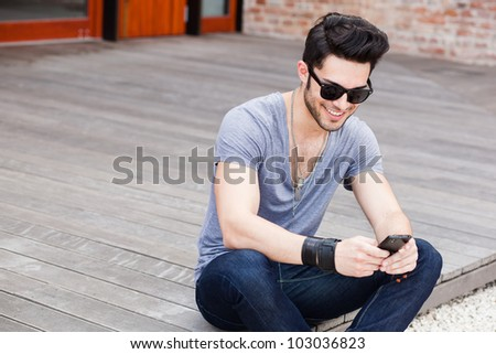 attractive young male model texting on a smartphone - stock photo