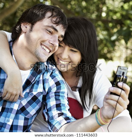 Attractive young male with beautiful young female having fun while smiling and listening to music - stock photo