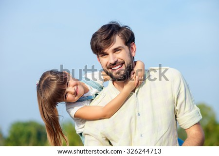 Attractive young man and his daughter are resting in the nature. The father is standing and carrying kid on his back. The girl is embracing him. They are looking forward and smiling - stock photo