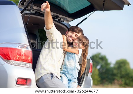 Attractive young man and his daughter are sitting on car trunk in the nature. They are embracing and smiling. The parent is pointing finger sideways. The girl is looking there with joy - stock photo