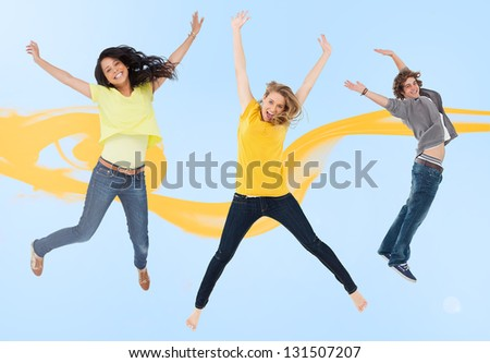 Attractive young man and women jumping for joy with yellow smoke trail on blue background - stock photo