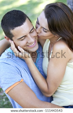 Attractive young man being kissed by beautiful young lady - stock photo
