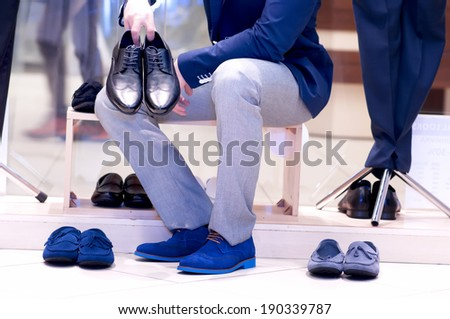 Attractive young  man chooses a shoes  at a shop.  - stock photo