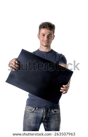 Attractive young man holding and showing empty, blank black board, sign or paper sheet - stock photo