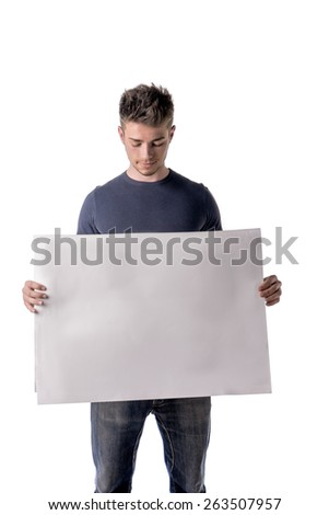 Attractive young man holding and showing empty, blank white board, sign or paper sheet - stock photo