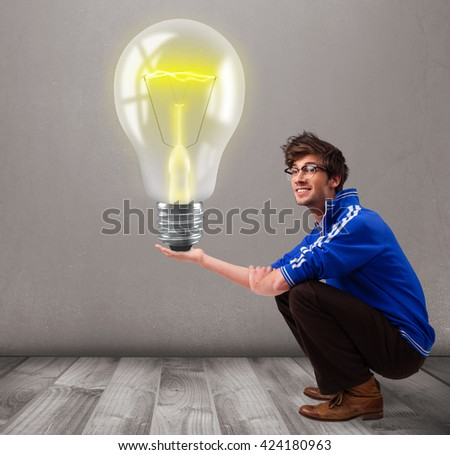 Attractive young man holding realistic 3d light bulb - stock photo