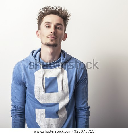 Attractive young man in a blue sports sweater pose in studio.  - stock photo