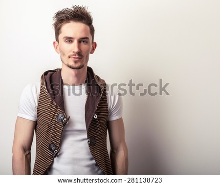 Attractive young man in a brown vest and white t-shirt  pose in studio.  - stock photo