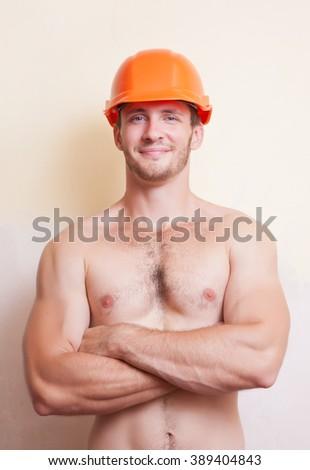 Attractive young man in an orange construction helmet - stock photo