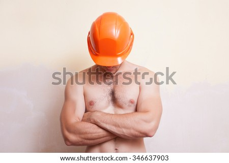 Attractive young man in an orange construction helmet with a naked torso - stock photo