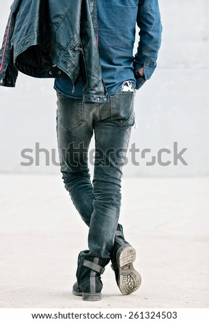Attractive young man in back with smartphone in his pocket - stock photo