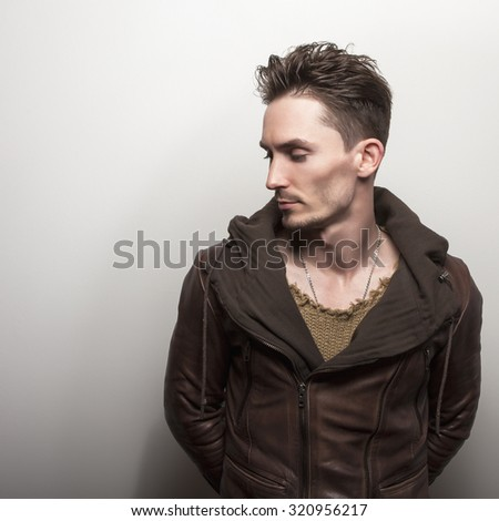 Attractive young man in brown leather jacket pose in studio.  - stock photo