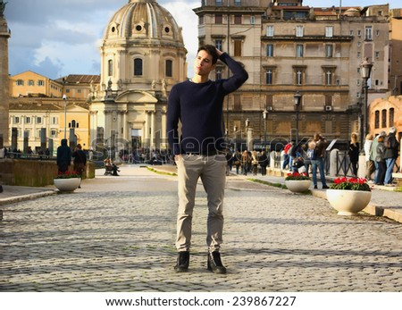 Attractive young man in Rome standing in front of Santa Maria di Loreto church, looking away - stock photo